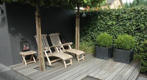 Kleine achtertuin met vlonder, split en Oud Hollandse tegels