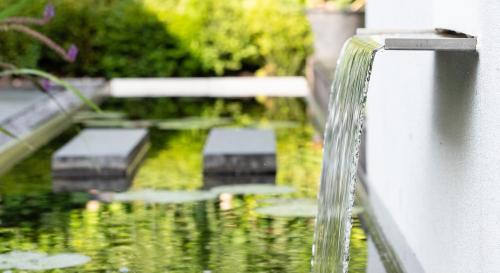 Moderne tuin met spiegelvijver en buitenhaard